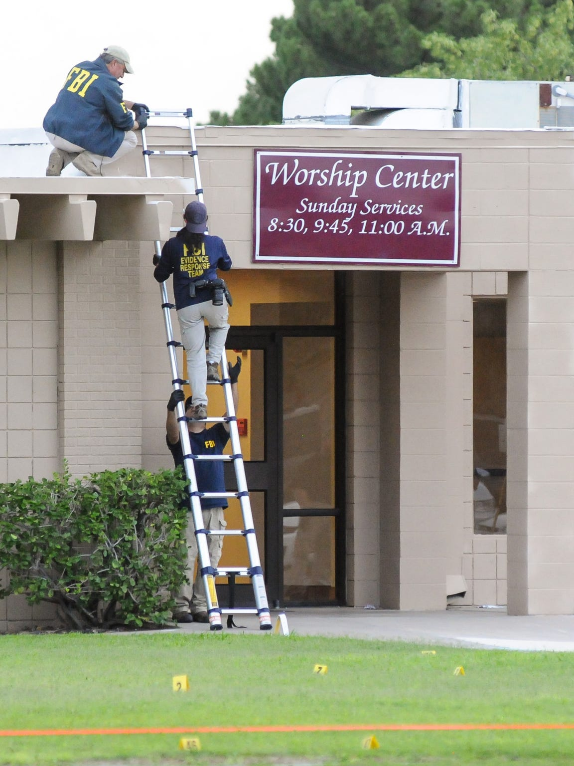 Members of the FBI climb onto the roof of Calvary Baptist