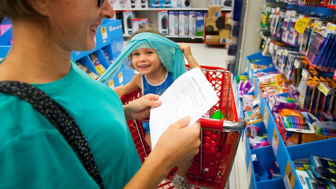 Hazel DeCosta, 3, helps her mother, Kelly Young, with back-to-school shopping Friday at Target in Fort Myers. Friday was the start of Florida's sales tax-free holiday shopping period, which lasts until Aug. 16 for certain items such as clothes, shoes, school supplies and computers, without worrying about paying the state's 6 percent sales tax.