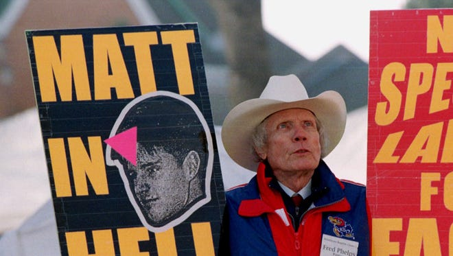 Fred Phelp wields placards protesting homosexuality outside the Albany County Courthouse in Laramie, Wyo., April 6, 1999, ahead of the trial of one of the defendants in the beating murder of gay University of Wyoming student Matthew Shepard.
