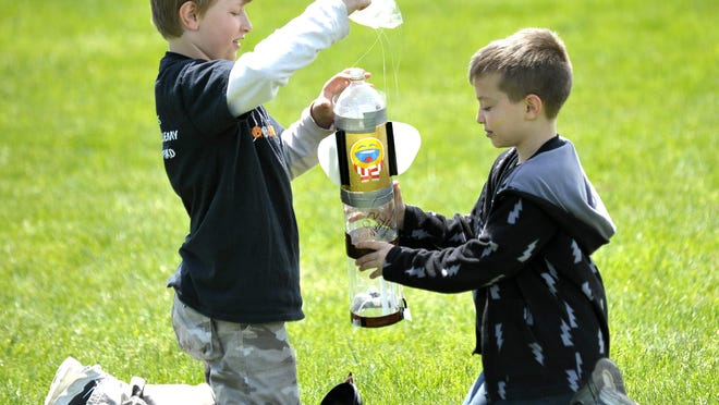 Mt. Clemens Montessori Academy third grader Stephen Krause, left, 9, of Mount Clemens, and fifth grader Alex Cartagena, right, 10, of Clinton Township, repack their water bottle rocket parachute before firing it again.