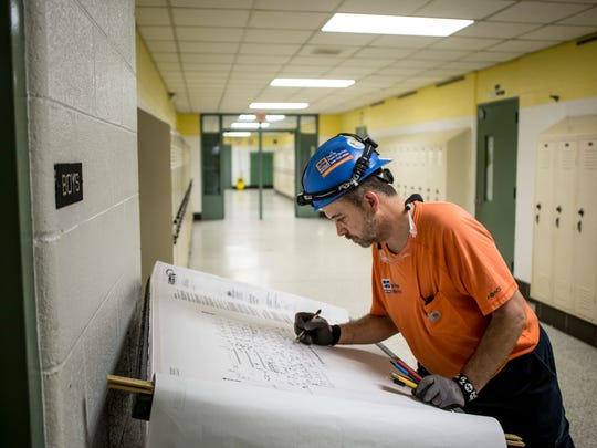 Contractor Greg Music looks over blueprints while working