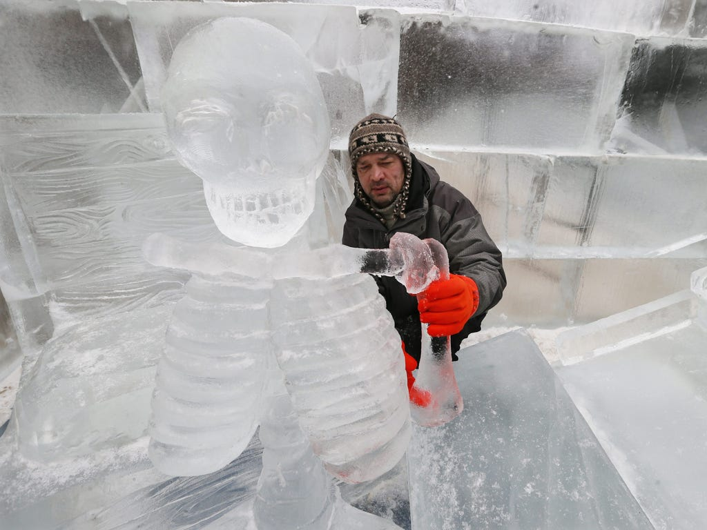 An artist fixes a limb for an ice sculpture in Moscow, Russia on Dec. 5. Six ice carvers from Russia and Poland are creating an ice labyrinth from 70 tons of ice for Christmas and New Year celebrations.