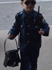 Caleb Chatham, dressed a police officer, stopped by The Advocate to help fill his bucket with candy.
