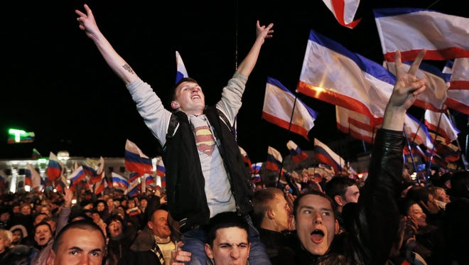 People react on Lenin Square after the end of a referendum in Simferopol, Crimea, March 16, 2014.
