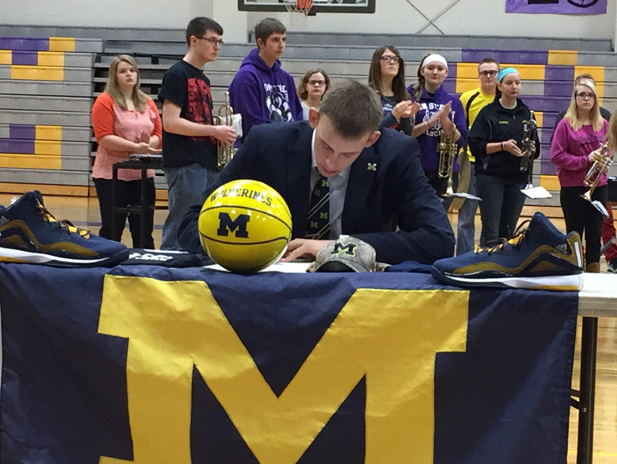 Onsted center Austin Davis signs his national letter of intent with Michigan on Wednesday, Nov. 11, 2015.