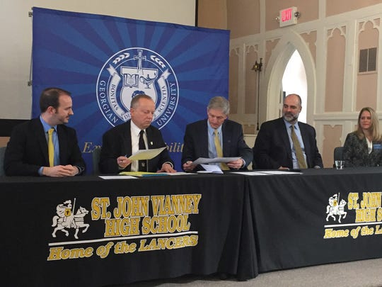 Saint John Vianney President  Joseph Deroba, second from left, signs an agreement with Georgian Court University President Joseph Marbach, third from right.