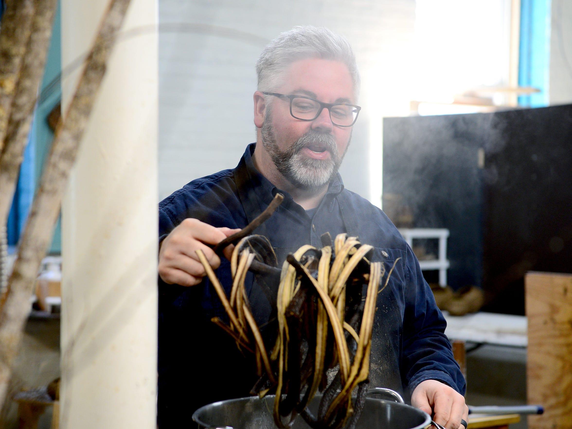 Artist Matt Tommey pulls weaving materials out of a