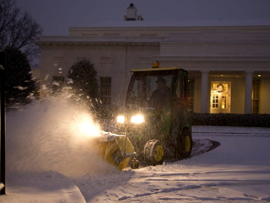 A United States Park Service employee clears snow from