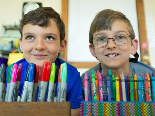 "Jacob Taylor, left, 9 and Max Taylor, 11, who are participating in a kids' entrepreneur course, are pictured on Monday, April 10, 2017, at Action Academy with their pen holder products. The two boys are selling assorted wood products and they named their store, ""Taylor Brother Enterprises""."