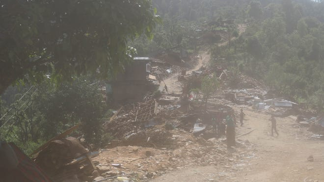 The road on the way to the Katunge region winds its way past destroyed homes.