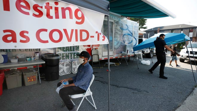 Ricardo Sojuel waits for a coronavirus swab as workers start to dismantle a mobile COVID-19 testing unit, Thursday, July 2, 2020, in Lawrence.