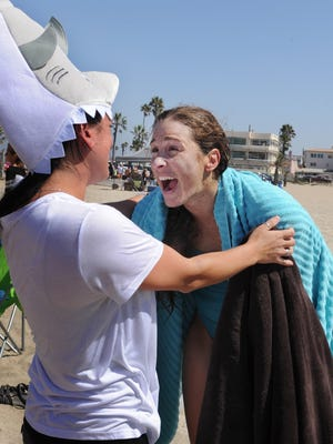 Rachel Horn, right, is greeted by her friend Kristin Cresto after completing a 12.2 mile ocean swim from Anacapa Island to Silver Strand Beach on Saturday morning.