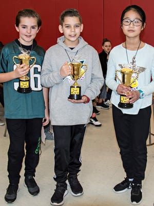 (From left) Travis Jenkins, third, Evan Crespo, second, and Grace Zheng, first, are the winners of the Millville Woman's Club's second annual spelling bee at Rieck Avenue School in Millville. Mark Goodson (not pictured) is the alternate who will fill in if any of the top three are unable to participate in the district level competition on Feb. 18.