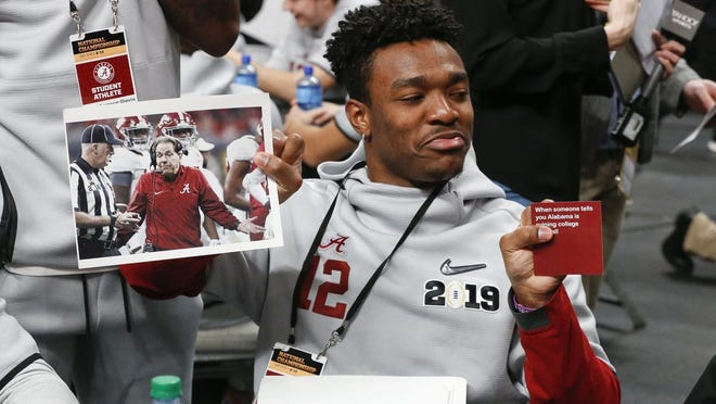 Alabama wide receiver Chadarius Townsend (12) holds up a photo of Coach Nick Saban as he plays a version of What Do You Meme during media day for the College Football National Championship Game in San Jose, California Saturday, Jan. 5 2019.