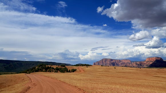 A smooth dirt road carves a winding path along the west side of Smith Mesa north of Virgin.
