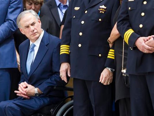 Texas Gov. Greg Abbott looks on as Kathleen Goforth receives the American flag that draped the casket during the funeral service for her husband Harris County Sheriff's Deputy Darren Goforth at Second Baptist Church, Friday, Sept. 4, 2015, in Houston.