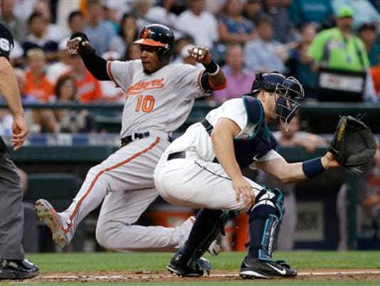 Seattle Mariners catcher Mike Zunino, right, waits for the ball as Baltimore's Adam Jones scores in the fourth inning on Monday night in Seattle. Baltimore won the game, 3-2.