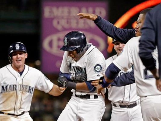 Seattle Mariners' Austin Jackson, center, is mobbed by teammates after hitting in the game-winning run against the Baltimore Orioles in the 10th inning of a baseball game Tuesday, Aug. 11, 2015, in Seattle. The Mariners won 6-5.