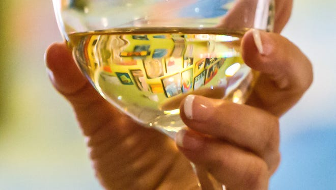 Paintings are seen through a glass of wine held by painter Lynn Kata Thursday, July 17, 2014, in La Grange, Illinois.