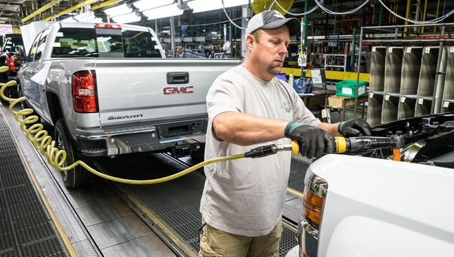 General Motors Flint Assembly employee Dan Hippensteel attaches the grille to the front of a GMC Sierra 2500 HD truck in August 2015.