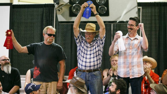 (Left to right) Second place winner Mike Adams, first place winner Ralond Troncin and third place winner Robb Witters hold up their ribbons for the mustache portion of the Art of Not Shaving - Mustache or Beard Contest at the Oregon State Fair on Monday, Aug. 29, 2016. Madison Rowley, the 2015 World Beard Champion, came from Portland to judge the contest.