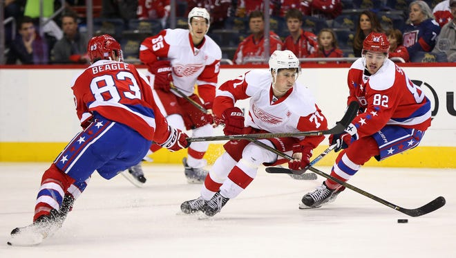 Red Wings center Dylan Larkin (71) battles for the puck with Capitals center Zachary Sanford (82) and Capitals center Jay Beagle (83) in the second period Friday in Washington.