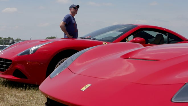 Jeff Hamilton, of Northville, looks out from the Ferrari show area during the Italian Happening car show and festival presented by Alfa Romeo on Sunday, June 11, 2017 at the M1 Concourse Race Track in Pontiac.