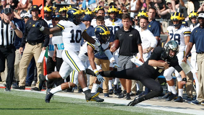Sep 23, 2017; West Lafayette, IN, USA; Purdue quarterback David Blough is pushed out of bounds by Michigan defensive back Tyree Kinnel and linebacker Devin Bush Jr. (10) at Ross-Ade Stadium.