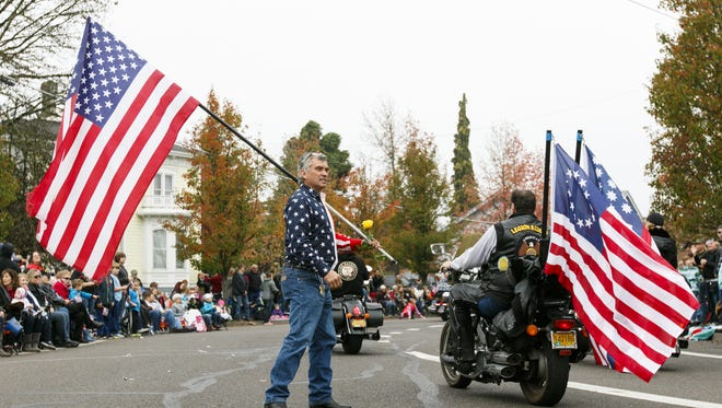 Johnny Garcia, of Veneta, Ore., thanks veterans for their service as they ride past at the start of the 65th annual Albany Veterans Day parade in 2016. Donate clothing to the Veterans Clothing Drive Nov. 4 to 12.