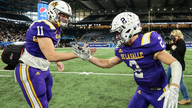 Warren De La Salle quarterback Luke Pfromm (11) celebrates with teammate wide receiver Jacob Badalamenti (2) after defeating Livonia Franklin 42-6 in the MHSAA Division 2 championship game at the Ford Field in Detroit, Friday, November 24, 2017.