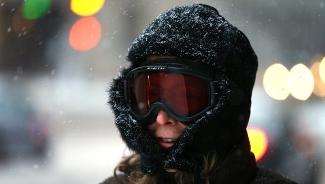 Teresa Goodson walks to work in ski goggles in downtown St. Paul during the first snowstorm of the season on Nov. 10, 2014.