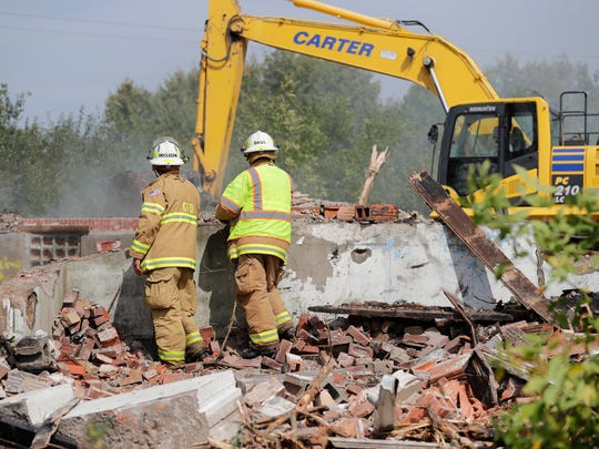 Greenleaf Fire Department personnel work to douse hotspots amid the rubble of the historic Lincoln School in Rockdale at the corner of Old Martin and Ryan Roads.