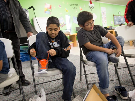 Urias Paez, left, and Ethan Lewis-Pete try on their new shoes and socks Friday at the Hilltop location for the Boys & Girls Clubs of Farmington.