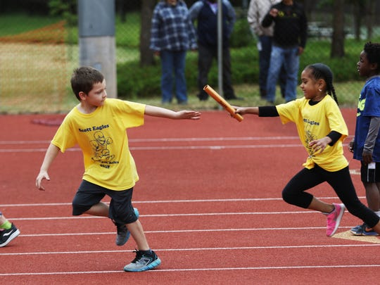 A first-grader from Scott Elementary School passes her teammate the baton at the 44th Annual COUNTRY Kids Relay at Willamette University's McCulloch Stadium on Saturday, May 19, 2018.