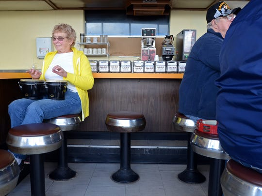 Bette Gall plays the drums while playing music inside Windchill Donut Shop on their last day Monday, Oct. 26, in Port Huron.