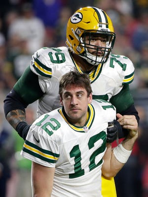 Green Bay Packers quarterback Aaron Rodgers (12) is pulled to his feet by guard Josh Walker after having his helmet knocked off during a sack against the Arizona Cardinals at University of Phoenix Stadium.