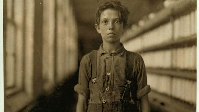 """Joe Manning's caption for this photo: Joseph Beaudoine, 14 years old. Lewis Hine's caption: Jo Bodeon. A """"back-roper"""" in mule room. Chace Cotton Mill, Burlington, Vt., May 1909."""
