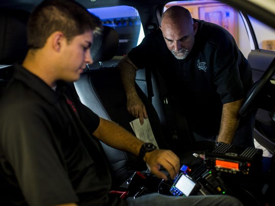 Cody Ellyson and Michael Hidalgo configure communications equipment in a police SUV at Barney's Police Supplies.