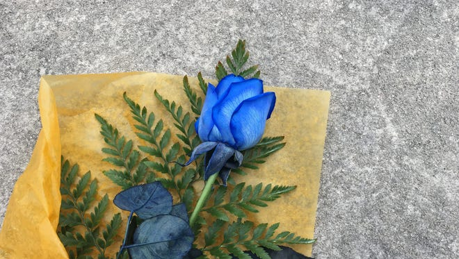 A single blue rose is left outside the Des Moines Police Department on Wednesday after two police officers were shot and killed overnight.
