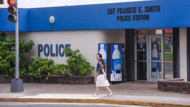 Tourists walk by the Sgt. Frankie E. Smith Police Station in Tumon on July 3, 2017.