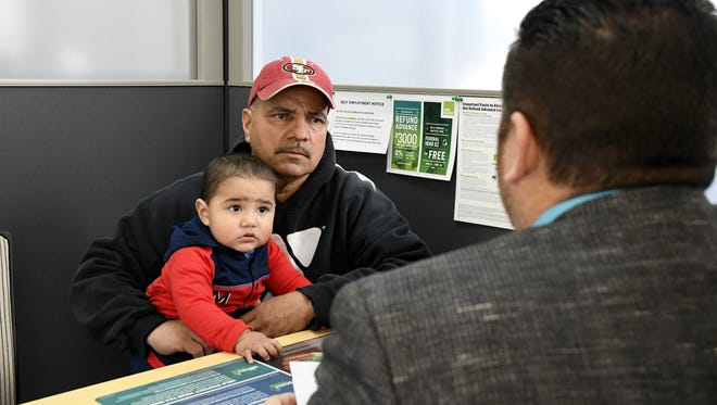 George Romero holds grandson Alec Romero during his meeting with Samuel Hernandez, a senior tax specialist, at H&R Block on Court Street in Visalia on Friday morning.