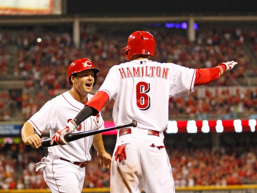 Cincinnati Reds left fielder Chris Heisey (28) celebrates with Billy Hamilton after scoring the eventual game-winning run.