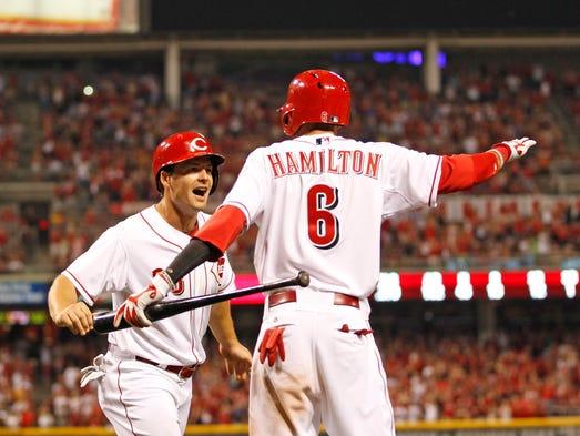 Cincinnati Reds left fielder Chris Heisey (28) celebrates with Billy Hamilton after scoring the eventual game-winning run.