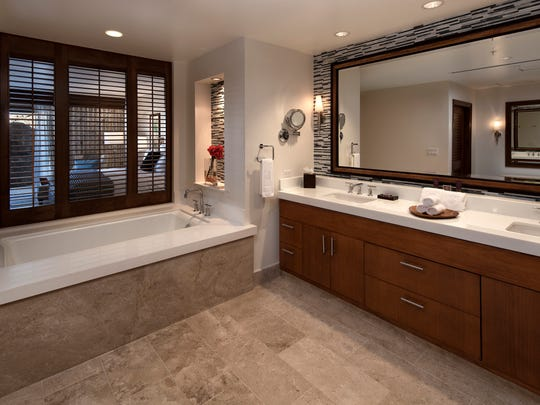 Like the kitchens, the bathrooms in the Ritz-Carlton Residences feature stone countertops and chestnut cabinets. Glass tile surrounds the mirror and space above the bathtub. All full bathrooms also include walk-in showers with glass doors.