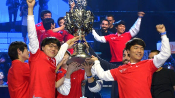 Members of South Korea's SK Telecom T1 team celebrate with their trophy after defeating China's Royal Club at the League of Legends Season 3 World Championship Final in Los Angeles. (AP Photo/Mark J. Terrill, File)