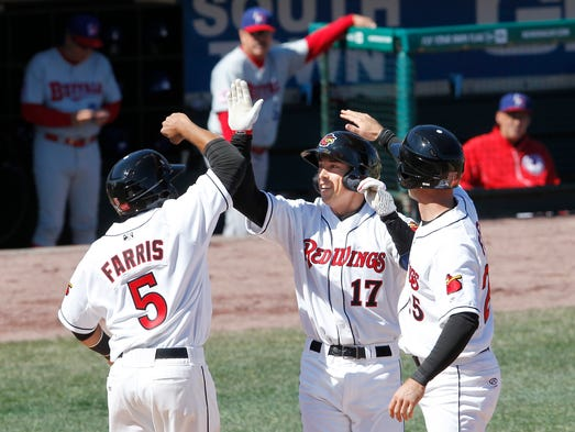 Rochester's Doug Bernier, center, gets congratulations from Eric Farris, left, and Eric Fryer after a 3-run home run during the home opener between the Buffalo Bisons and the Rochester Red Wings at Frontier Field Sunday.