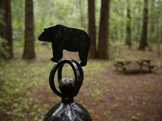 A bear figure sits atop a bell in the grove of the