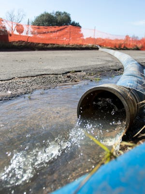 Water is pumped from the Corinne Jones Stormwater Pond and Park construction site to the storm drain on West Intendencia Street in Pensacola on Wednesday, January 11, 2017.