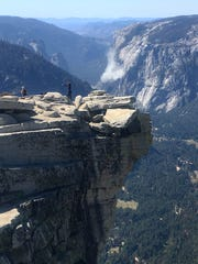 In this Wednesday photo provided John P. DeGrazio, a cloud of dust is seen in the distance on El Capitan after a major rockfall in Yosemite National Park
