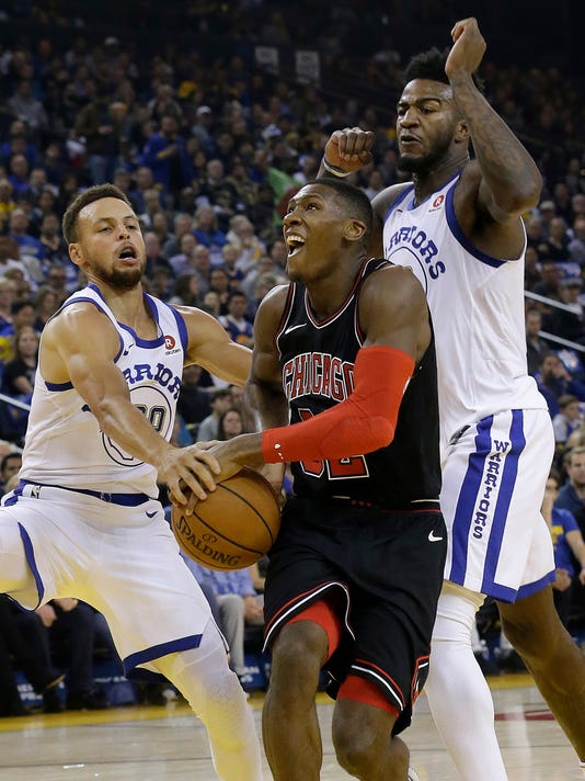 Chicago Bulls guard Kris Dunn, center, drives to the basket between Golden State Warriors guard Stephen Curry, left, and forward Jordan Bell during the first half of an NBA basketball game in Oakland, Calif., Friday, Nov. 24, 2017. (AP Photo/Jeff Chiu)